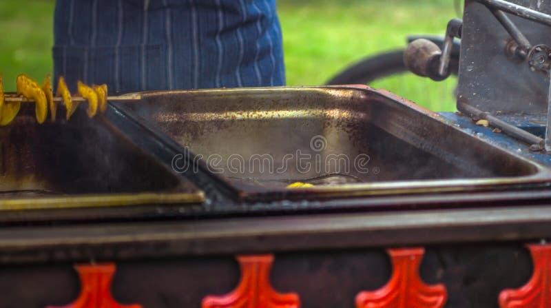 Gebratene Kartoffeln in Form von Spirale auf hölzernem Stock Kartoffeln gebraten bis goldene Farblügen auf Metallbehälter während stockfotografie