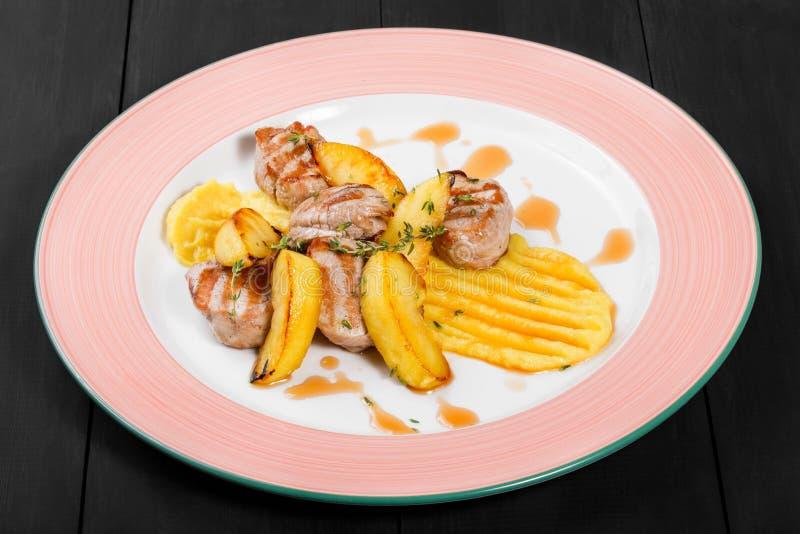 Gebratene Kartoffeln mit Hühnerfleisch und -kräutern in der Platte auf dunklem hölzernem Hintergrund stockfotografie