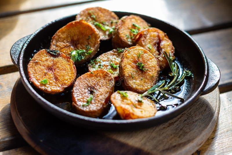 Gebratene Kartoffeln mit Rosmarin in einer kleinen Gusseisenwanne auf dem Tisch stockfotografie