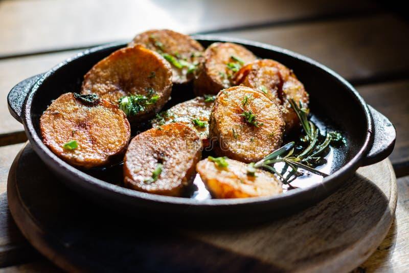 Gebratene Kartoffeln mit Rosmarin in einer kleinen Gusseisenwanne auf dem Tisch lizenzfreies stockbild