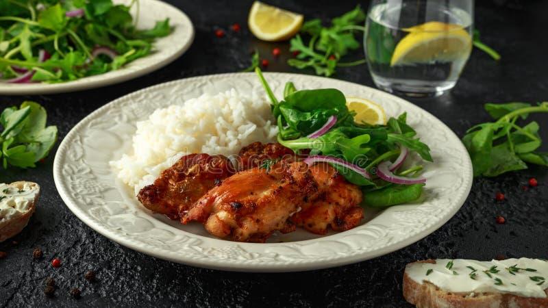 Gebratene knochenlose hautlose Hühnerschenkel mit Reis und grünem Gemüse mischen lizenzfreie stockfotografie