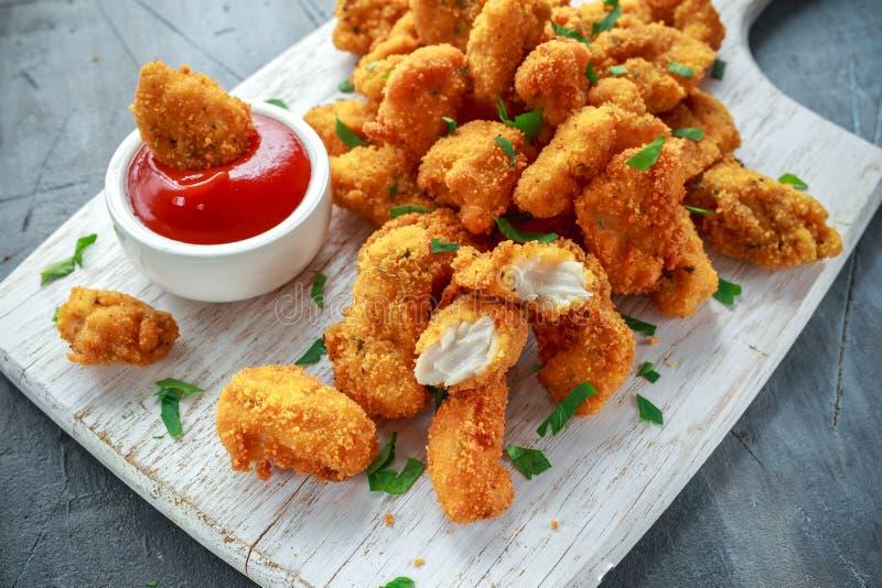 Gebratene knusperige Hühnernuggets mit Ketschup auf weißem Brett lizenzfreies stockfoto