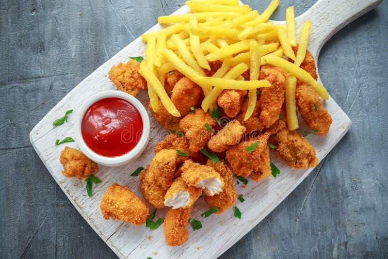 Gebratene knusperige Hühnernuggets mit Pommes-Frites und Ketschup auf weißem Brett lizenzfreies stockfoto