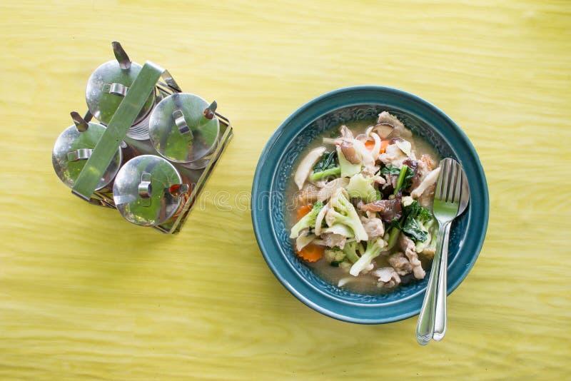 Gebratene Nudel mit Schweinefleisch und Brokkoli auf der grünen hölzernen Tabelle stockbild