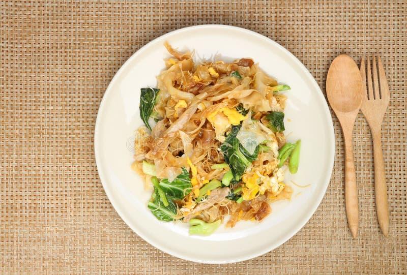 Gebratene Nudel mit Schweinefleisch und Brokkoli im schwarzen Schüsselplatz auf Holztisch mit Kopienraum für Ihren Text und Entwu lizenzfreies stockfoto