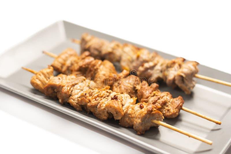 Gebratene Schweinefleischkebabs auf dem h?lzernen Stock dienten auf der Platte stockfotos