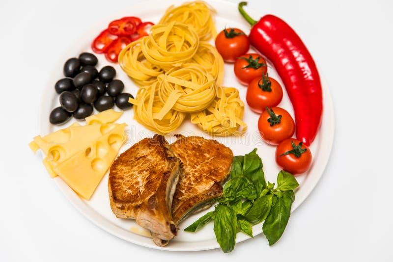 Gebratene Schweinefleischrippen mit Spaghettis, Kirschtomaten, Basilikum, Oliven, Peperoni und Käse lizenzfreies stockfoto