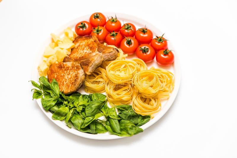 Gebratene Schweinefleischrippen mit Spaghettis, Kirschtomaten, Basilikum, Oliven und Käse lizenzfreies stockfoto