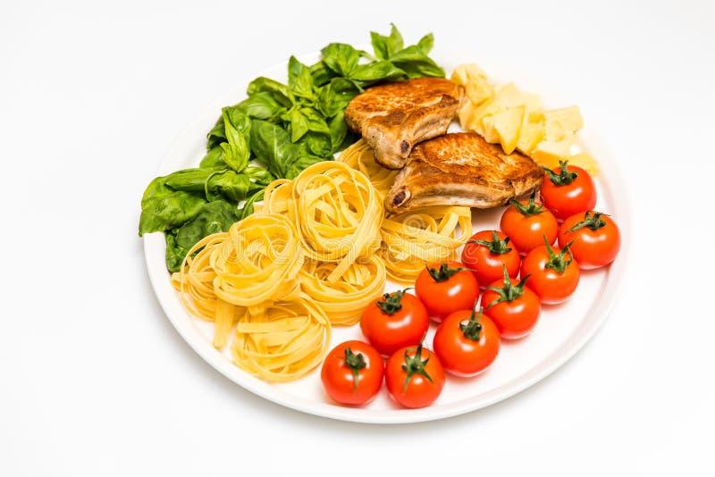 Gebratene Schweinefleischrippen mit Spaghettis, Kirschtomaten, Basilikum, Oliven und Käse lizenzfreie stockbilder