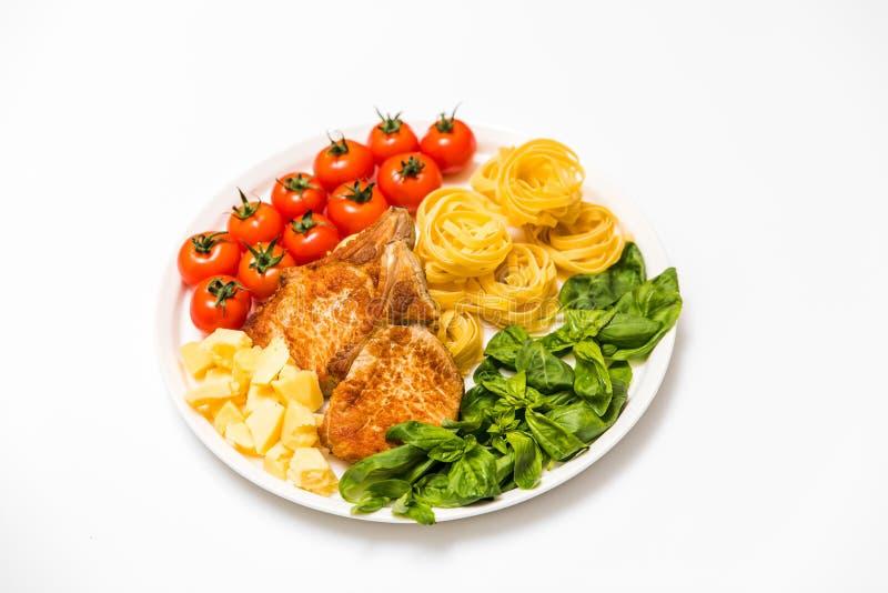 Gebratene Schweinefleischrippen mit Spaghettis, Kirschtomaten, Basilikum, Oliven und Käse stockfotos