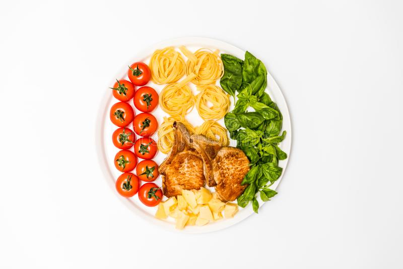 Gebratene Schweinefleischrippen mit Spaghettis, Kirschtomaten, Basilikum, Oliven und Käse lizenzfreie stockfotografie