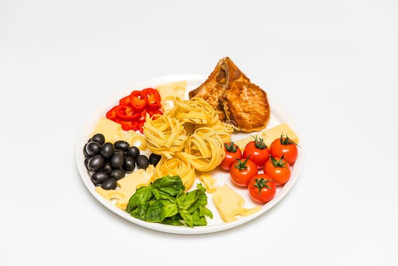 Gebratene Schweinefleischrippen mit Spaghettis, Kirschtomaten, Basilikum, Oliven und Käse stockbild