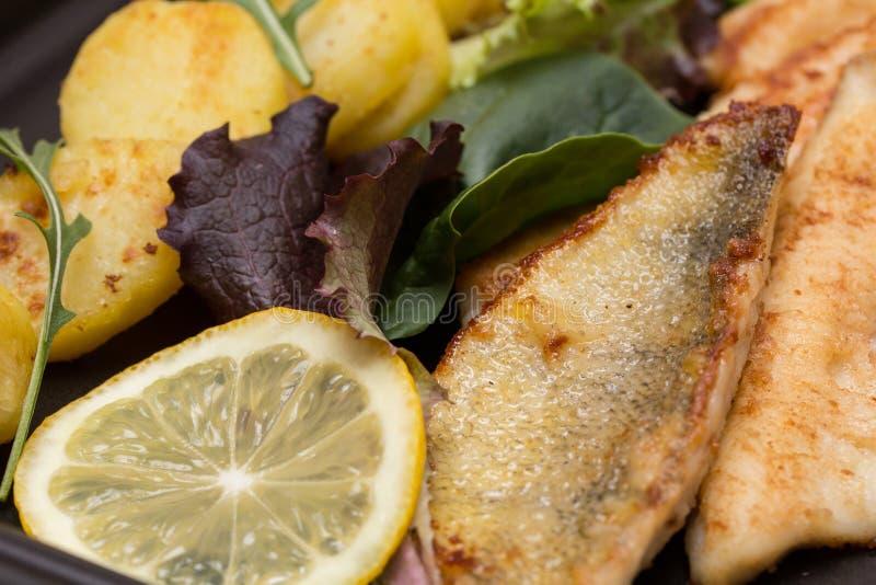 Gebratene Stangen-Verkleidungen mit gebratenen Kartoffeln, Zitrone und Salat stockfotos