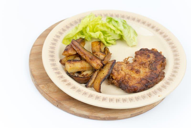 Gebratene Steakkartoffeln und -kopfsalat stockbild