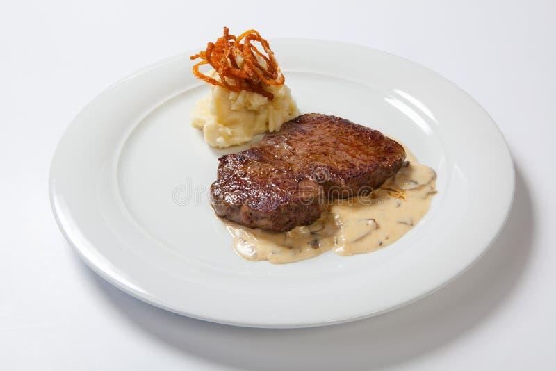 Gebratene Steaks mit Kartoffeln, gebratene Zwiebel und Sahnesauce stockbilder