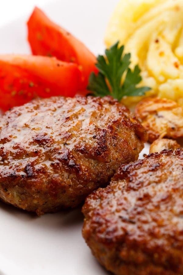 Gebratene Steaks mit Kartoffeln und gebratene Pilze stockfotografie