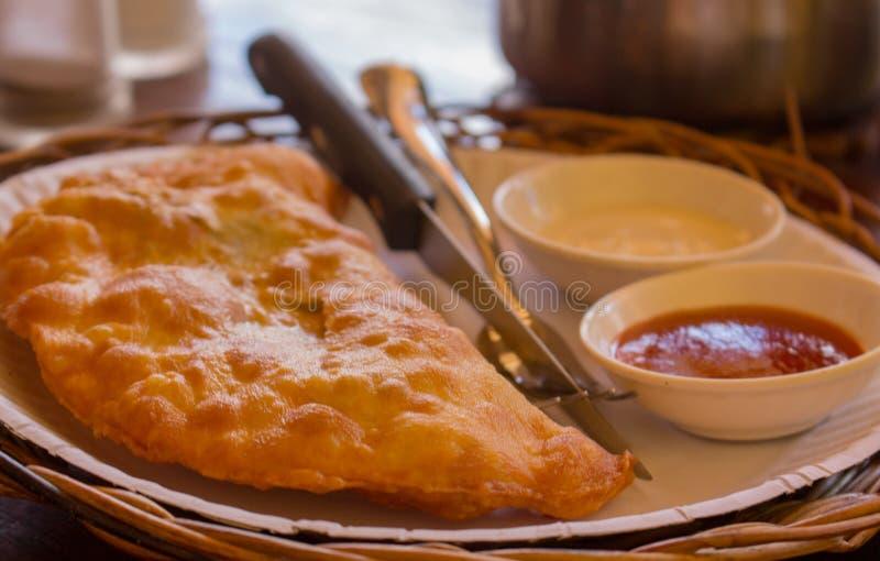 Gebratene Torte mit Fleisch und Soßen Heißes selbst gemachtes empanada Geschmackvolles Pastetchen Traditionelle ukrainische Nahru lizenzfreies stockfoto