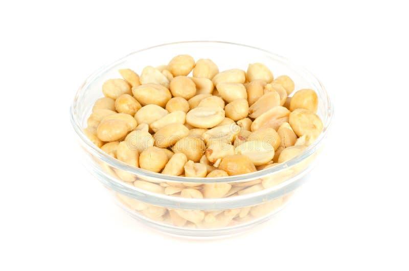 Gebratene und gesalzene Erdnüsse in der Glasschüssel über Weiß stockfoto
