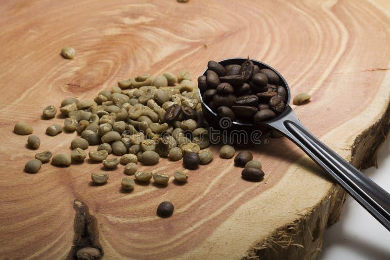 Gebratene und Rohkaffeebohnen auf einer Wacholderbuschplatte stockfoto