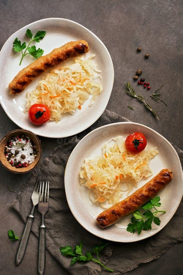 Gebratene W?rste mit Sauerkraut auf einem dunklen rustikalen Hintergrund Flache Lage, Kopienraum lizenzfreies stockfoto