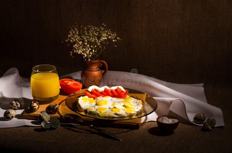 Gebratene Wachteleier mit Tomaten und Majonäse, auf einer Platte stockbilder