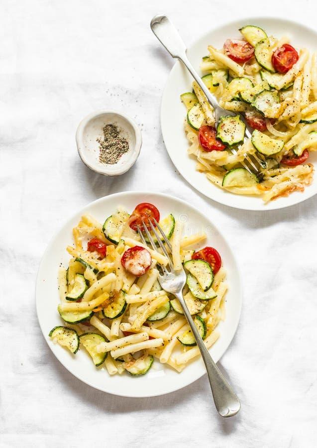 Gebratene Zucchini- und Kirschtomaten backten Mac und Käse auf dem hellen Hintergrund, Draufsicht Vegetarisches gesundes Mittages lizenzfreies stockfoto