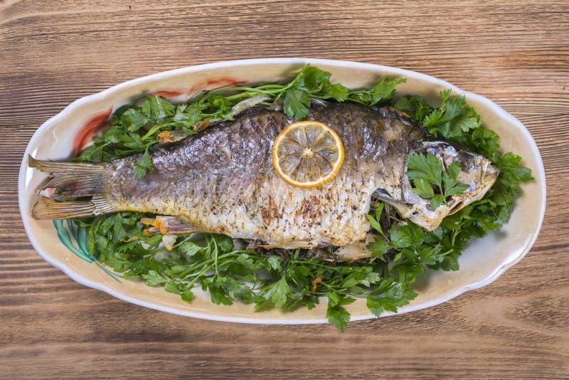 Gebratener Fischkarpfen in der Platte auf hölzernem Hintergrund, Abschluss oben lizenzfreie stockfotos