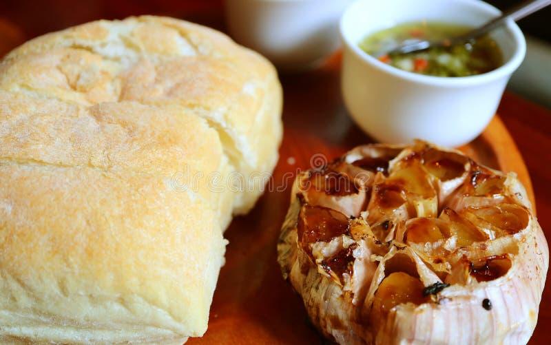 Gebratener Knoblauch und gebackenes weiches Brot mit Bad auf hölzerner Platte stockfotografie