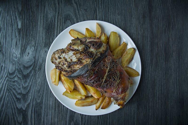 Gebratener Schweinefleischkn?chel diente mit den Kartoffeln, die auf einer wei?en Platte gedient wurden Dunkler h?lzerner Hinterg stockbilder