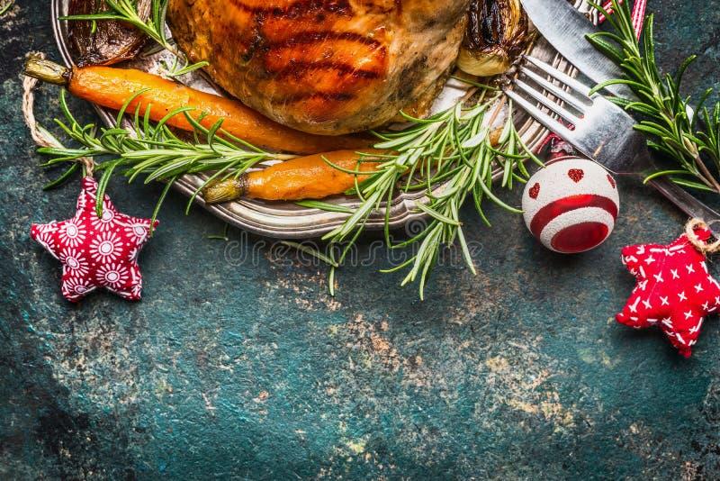Gebratener Schweinefleischschinken auf silberner Platte mit Gemüse, Tischbesteck und Weihnachtsdekoration, Draufsicht stockbild