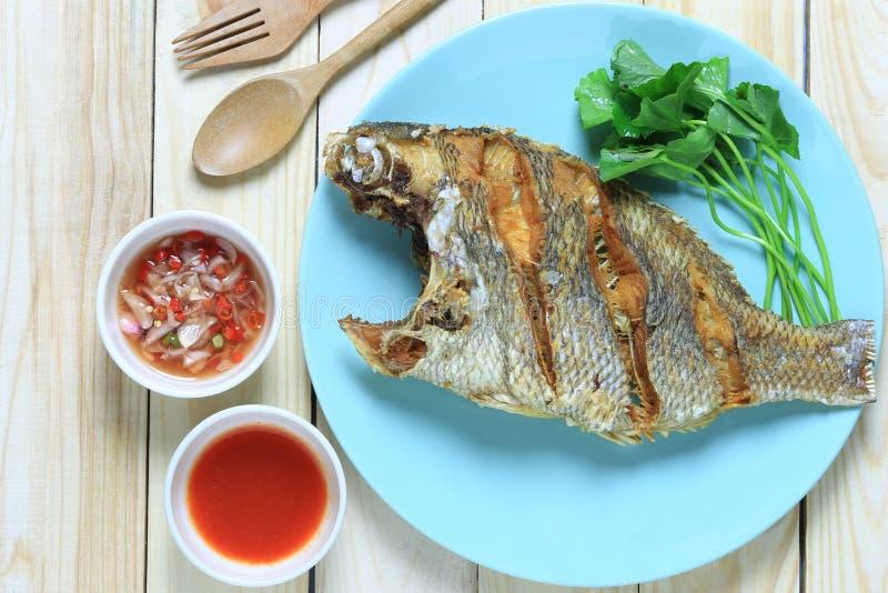 Gebratener Seefisch im Teller auf Bretterboden und thailändischer Gewürzsoße lizenzfreie stockbilder
