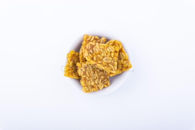 Gebratener tempeh oder Sojabohnenkuchen in der weißen Schüssel über einem weißen Hintergrund lizenzfreie stockfotos