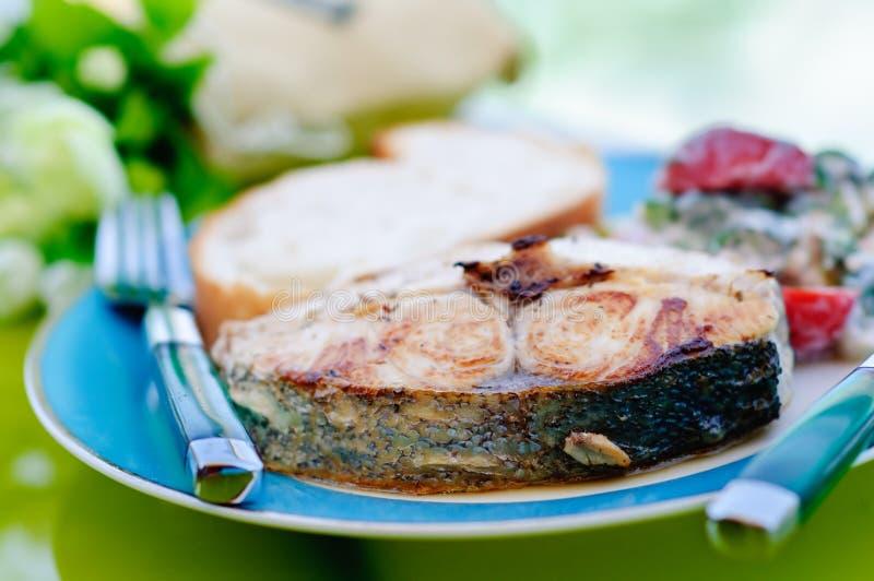 Gebratener Thunfisch mit einem Messer und Gabel auf dem Teller lizenzfreies stockbild