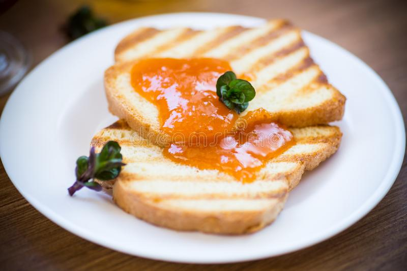 Gebratener Toast mit Aprikosenmarmelade in einer Platte stockbild