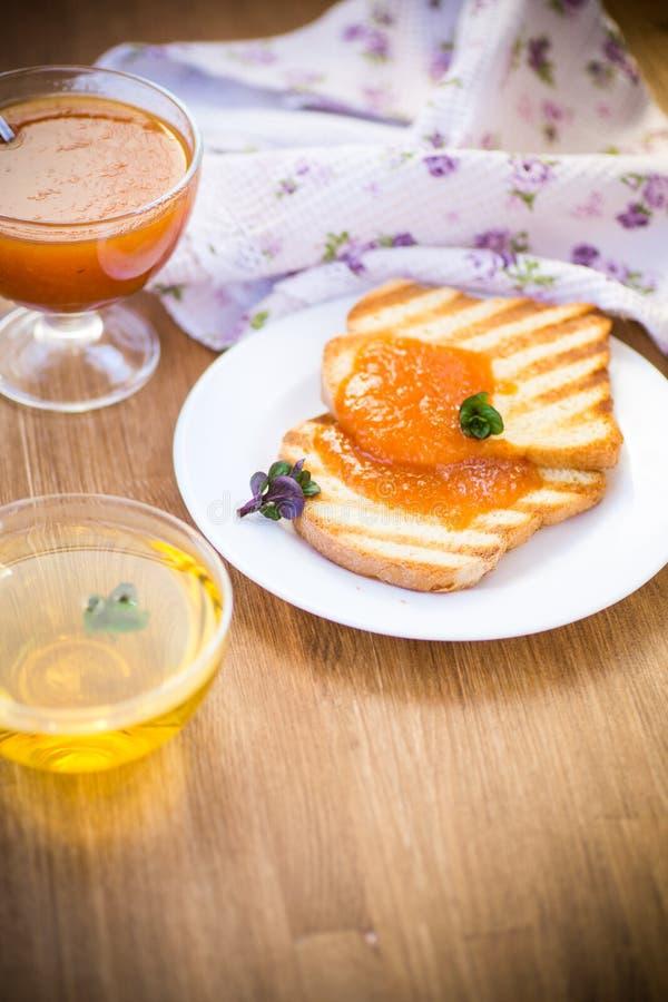Gebratener Toast mit Aprikosenmarmelade in einer Platte stockbilder