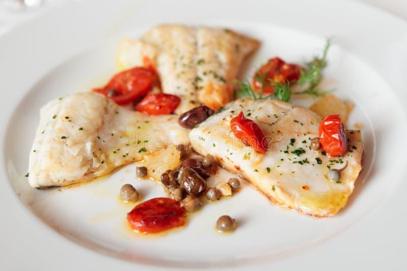 Gebratenes Fischfilet mit Kapriolen und Tomaten lizenzfreies stockbild