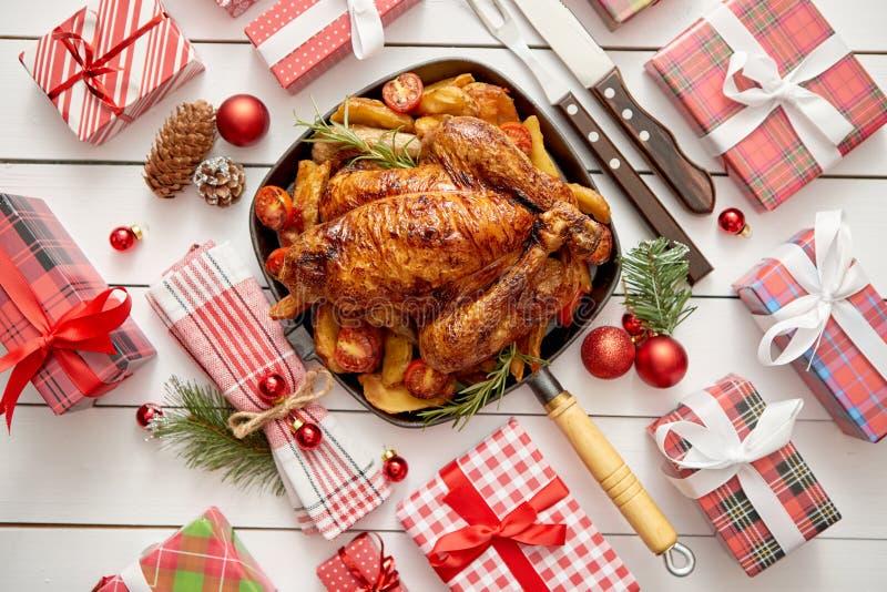 Gebratenes ganzes Huhn oder Truthahn dienten im Eisenstein mit Weihnachtsdekoration stockfoto