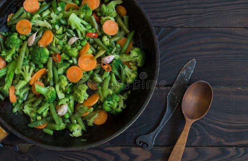 Gebratenes Gemüse in einer Bratpfanne auf einem dunklen Holztisch lizenzfreie stockfotografie