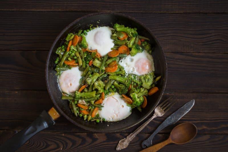 Gebratenes Gemüse und Eier in einer Bratpfanne auf einem dunklen Holztisch lizenzfreie stockbilder