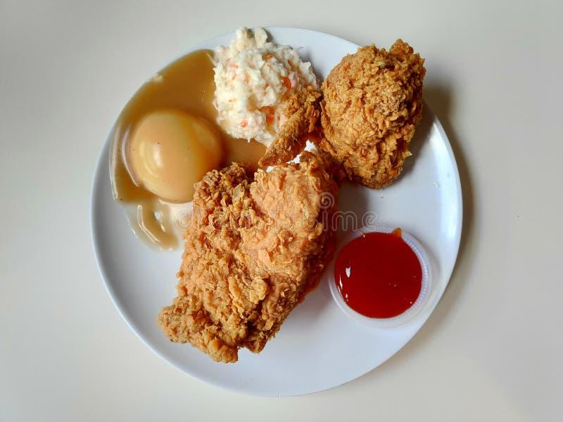 Gebratenes Hühneraufschlag mit Huhn, Kohlsalat, Kartoffelpüree mit Soßensoße und Chili-Sauce auf weißer Platte stockbild