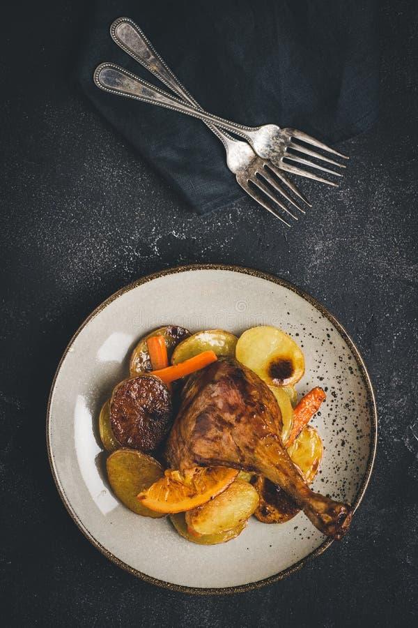 Gebratenes Hühnerbein mit Kartoffeln, Karotten und Orangen lizenzfreie stockfotos