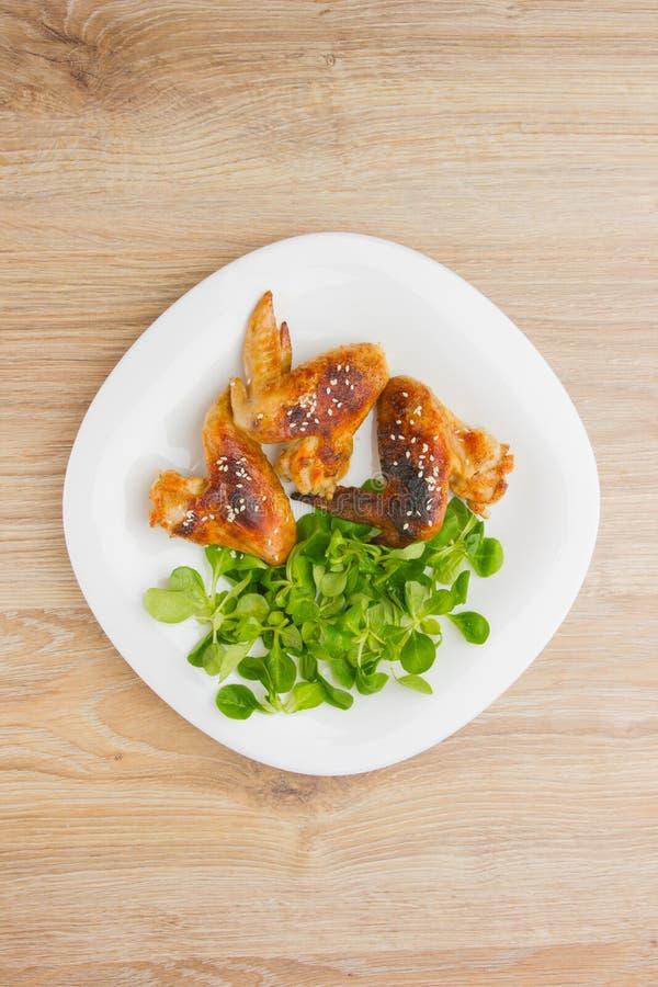 Gebratenes Hühnerflügel Hühnerflügel eines Grills auf einer weißen Platte mit Salat lizenzfreie stockbilder