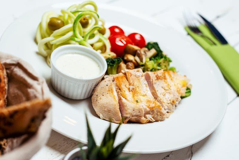 Gebratenes Hühnerleiste und Frischgemüsesalat von Tomaten, von Gurken und von Brokkoli stockfotos