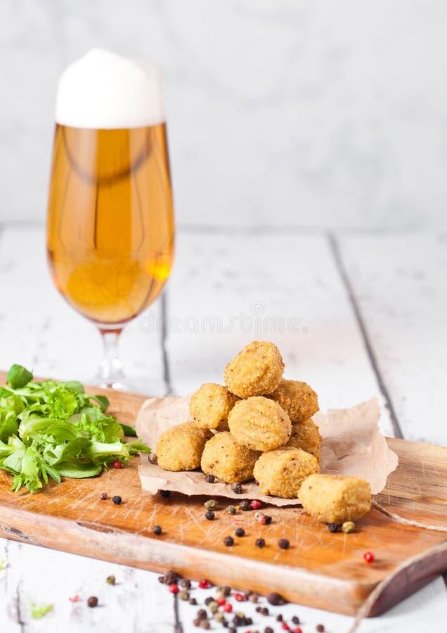 Gebratenes Hühnerpopcorn mit frischem Salat und Bier stockfotos