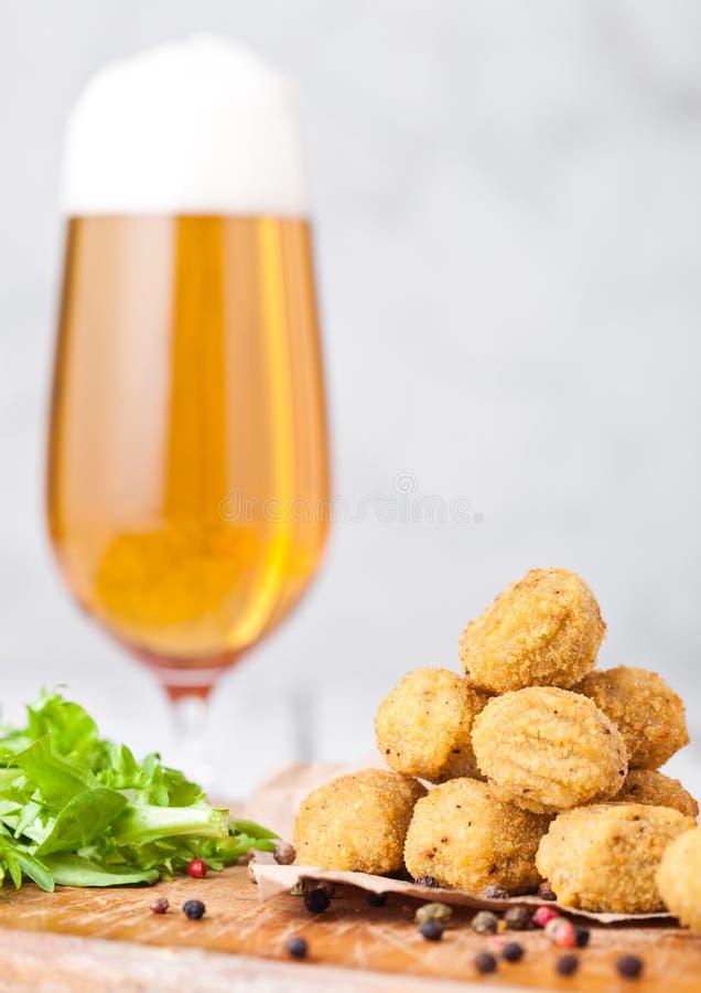 Gebratenes Hühnerpopcorn mit frischem Salat und Bier stockfotografie