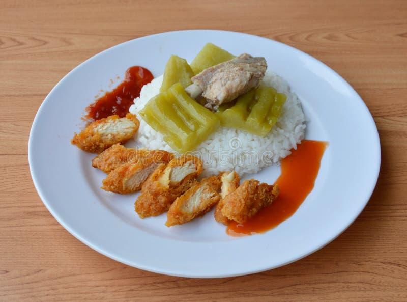 Gebratenes Hühnerscheibe und gekochte bittere Gurke mit dem Schweinefleischknochen auf Reis lizenzfreies stockbild