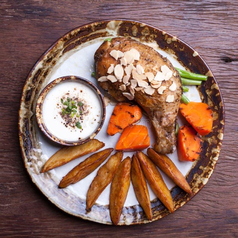 Gebratenes Hühnertrommelstöcke mit Kartoffel zwängen, Karotte auf Platte lizenzfreie stockfotografie