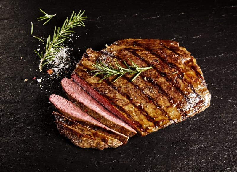 Gebratenes halb gares geschnittenes Flankenrindfleisch mit Rosmarin stockbild