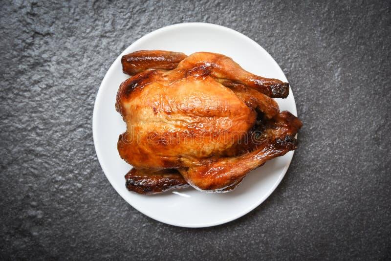 Gebratenes Huhn backte das ganze Huhn, das auf weißer Platte und dunklem Hintergrund auf Draufsicht gegrillt wurde stockfotografie