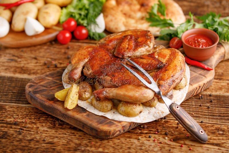 Gebratenes Huhn mit einem Schmückung von gebackenen jungen Kartoffeln Hühnertabak und eine vorzügliche Gabel Appetitanregendes St lizenzfreie stockfotos